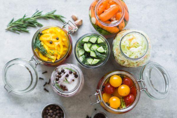 Pickled vegetables. Salting various vegetables in glass jars for long-term storage. Preserves vegetables in glass jars. Variety fermented green vegetables on table.